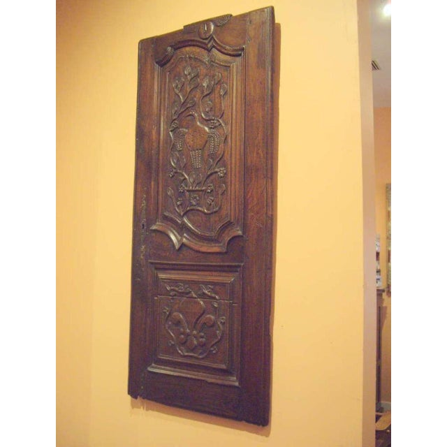 Lovely 18th century chestnut French Provincial door panel. Very nice on the wall with the whimsical design of the carving....