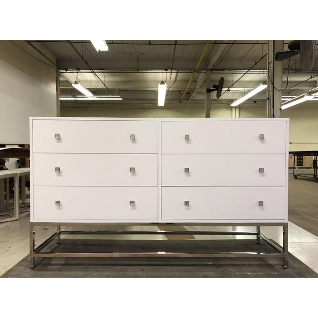 The details six drawer tall dresser is a first quality sample that features a cloud finish with polished nickel square...