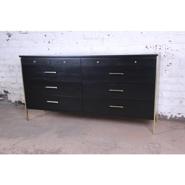 Offering a stunning ebonized Paul McCobb for Calvin Furniture ten drawer long dresser. The dresser distinguished brass...