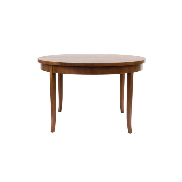 An elegant, graceful round dining table designed by T.H. Robsjohn-Gibbings for Widdicomb. Perfectly patterned walnut forms...