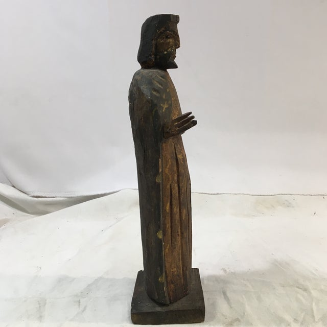 This is an antique figure of Jesus that was hand-carved from wood and hand-painted. The figure's shoulder-length brown...