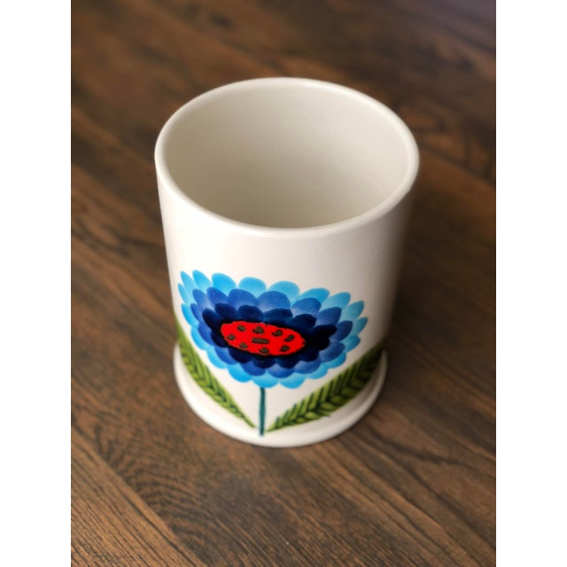 An eye catching white ceramic pot with a striking single flower. The simple flower design in blues, greens, and red poppy...