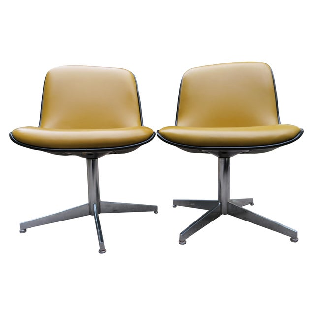 A pair of vintage Steelcase swivel slipper chairs. Dark gold vinyl with double top stitching. Molded plastic frame on...