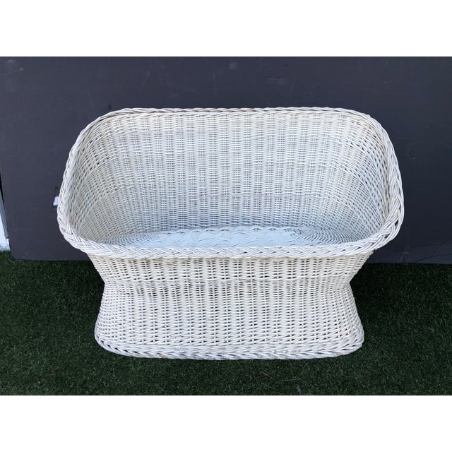 Vintage 1970s woven rattan tub settee. Loveseat sized to fit two, woven rattan base has rounded silhouette with braided...