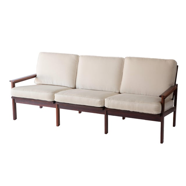 A newly reupholstered sofa in the style of Finn Juhl. A glowing exotic rosewood frame. Sturdy with webbing and loose...