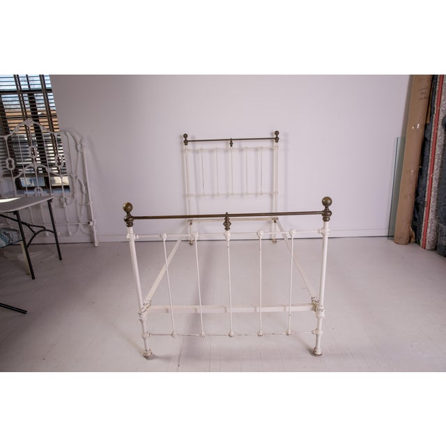 A Madcap Cottage white-painted early Victorian iron bed with brass metal details brought back from a country house sale in...