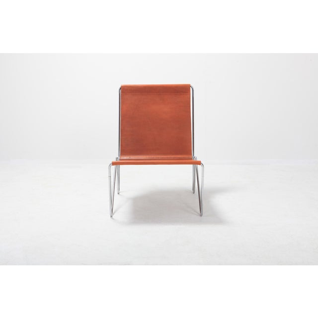 Fritz Hansen manufactured easy chair by Verner Panton. A minimal tubular steel frame with suspended cognac leather....