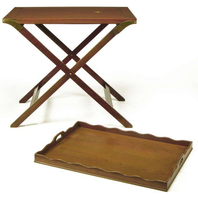 Butler tray table, with folding X-base, in original light walnut finish from Baker Furniture. Two flush panel mahogany...