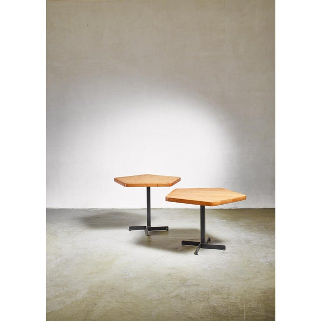 A pentagonal dining or coffee table by Charlotte Perriand. The table has a black lacquered metal base with a pine top. It...