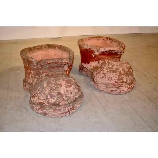 Pair of large terracotta planters in the shape of a pair of shoes.