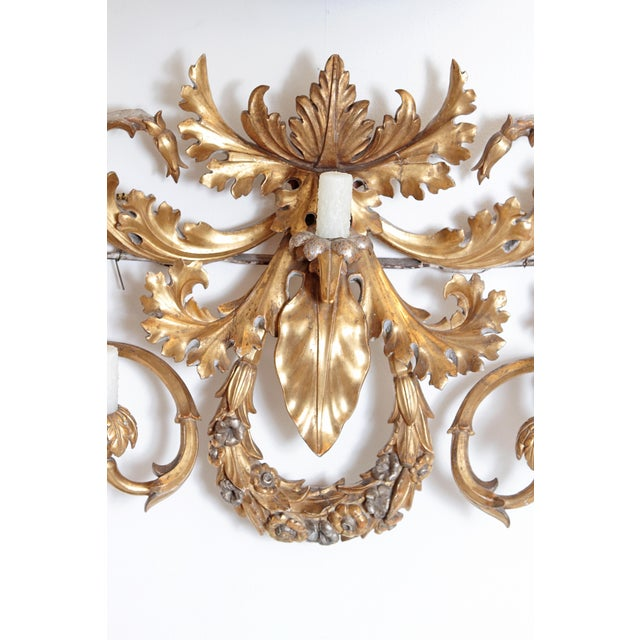 an oversized / large seven-arm gilt carved-wood and gesso wall sconce, gilded gold with silver accents, Baroque-style,...