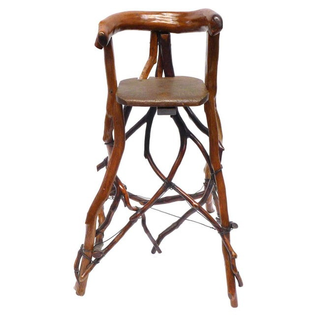 An unusual and beautiful high chair of twig-construction with a wire support structure laced throughout. A rough-yet-...
