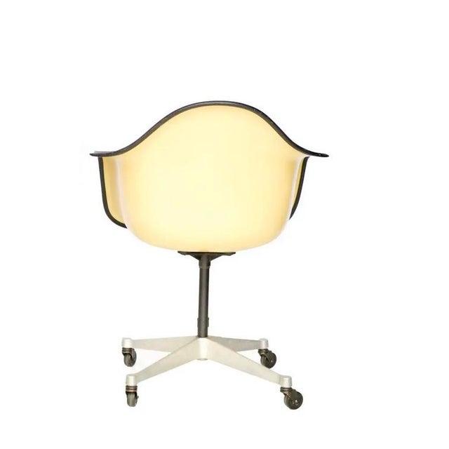 Early Herman Miller Eames upholstered fiberglass arm chair on aluminum caster bases. Swivel action. naugahyde on the back...