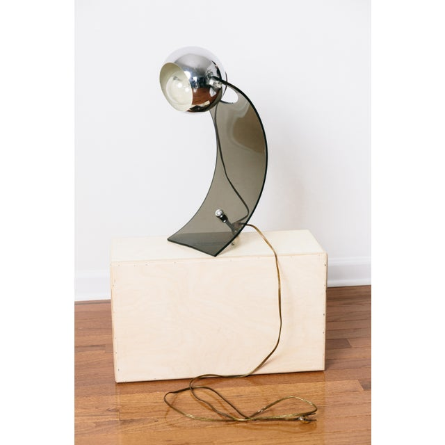 A fabulous mid-century smoked lucite and chrome eyeball table lamp in the style of Robert Sonneman.