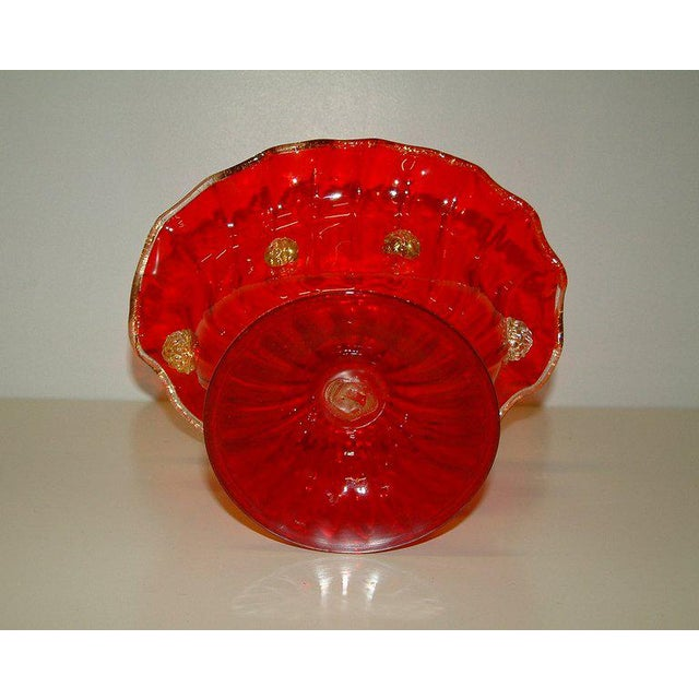 A stunning Murano compote of ruby red glass with gold inclusions on applied cluster rosettes and rim. The piece is...