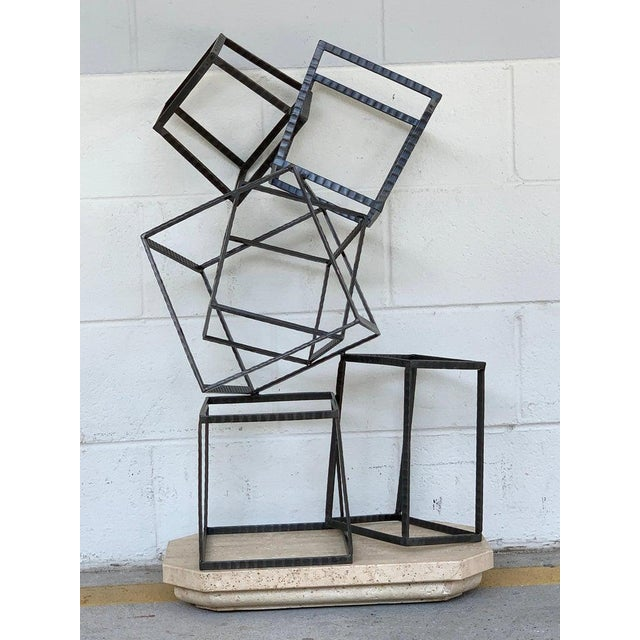 Modern forged iron and travertine quadrilaterals sculpture, with six balancing cubes of varying geometric shapes, raised...