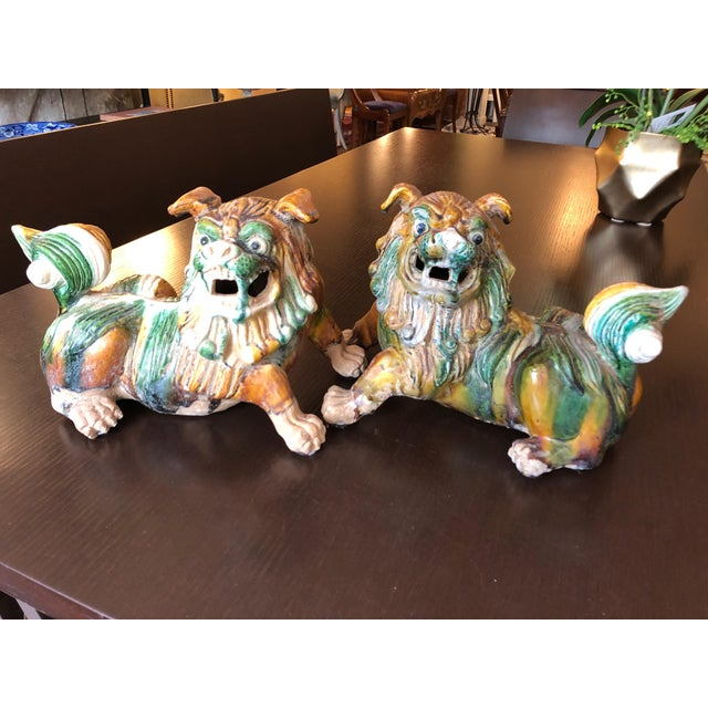 Wonderful pair of chunky earth colored ceramic foo dogs in green, ochre, gold and cream. Made in the 1950s.