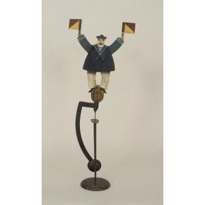 American Country (19/20th Cent) Folk Art toy of a painted and decorated sailor holding two flags mounted on an iron...