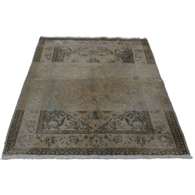 This hand-knotted wool vintage rug of Persian origin and Kashan design features a full-length medallion rendered in gray...
