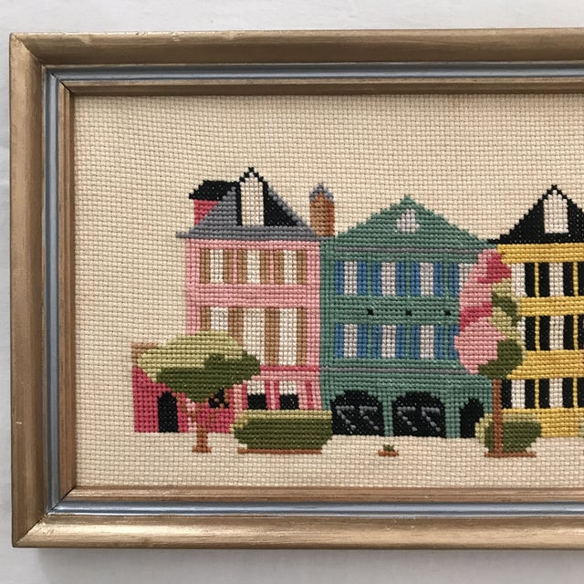 Charming framed needlepoint art displaying a colorful view of historic Rainbow Row in Charleston, South Carolina - a...