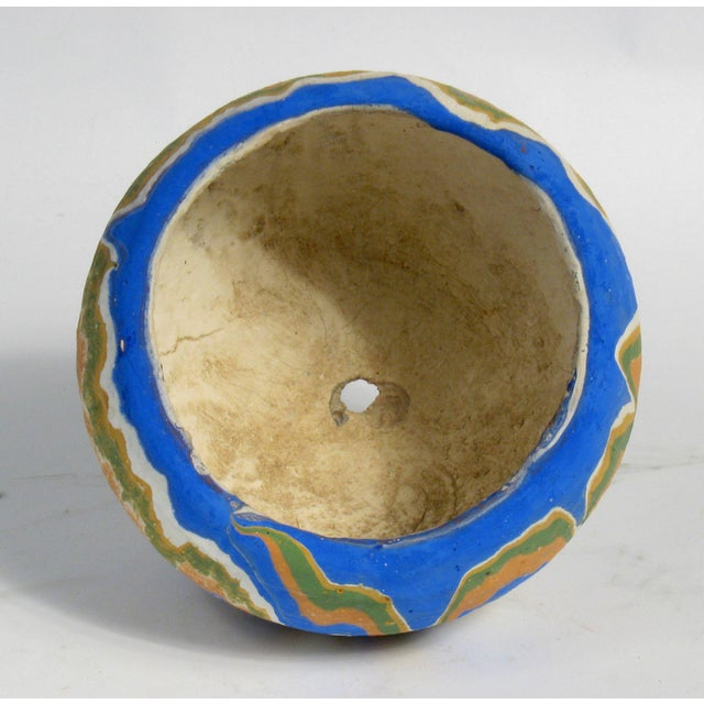 Heavy earthenware pot with painted abstract pattern in Southwestern palette.