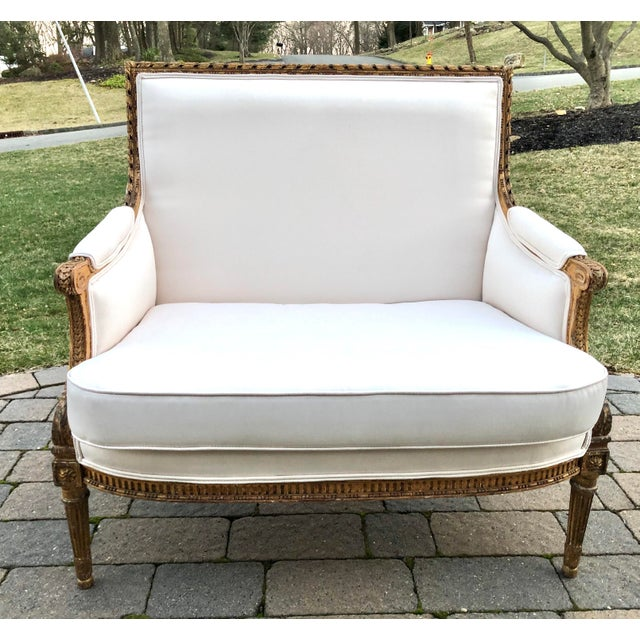Gilt Wood Upholstered Carved French Louis XVI Style Loveseat. The loveseat includes white fabric and a gold frame.