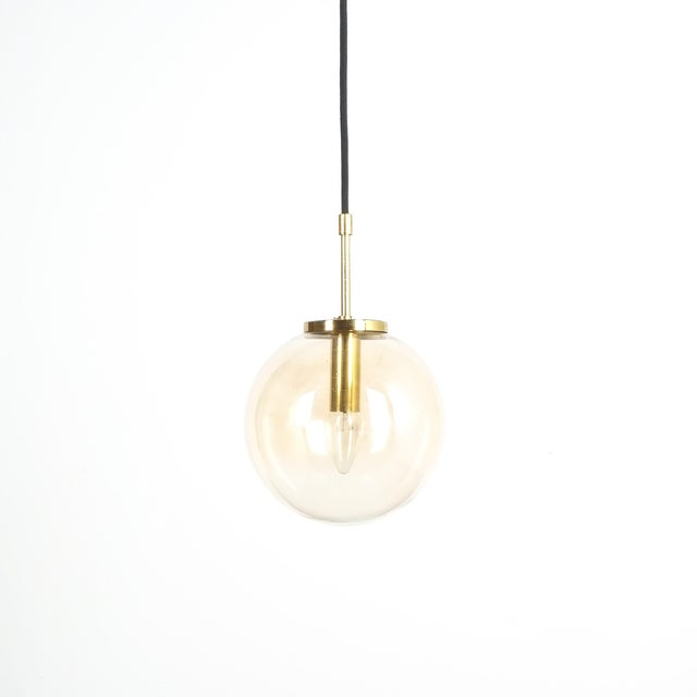 Limburg amber glass pendant light fixtures with brass hardware and black cloth cord wire. Excellent condition, newly...