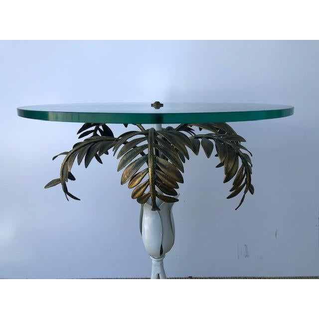 Rare Hollywood Regency table with palm frond details in metal. Round glass top complements this beautiful design.