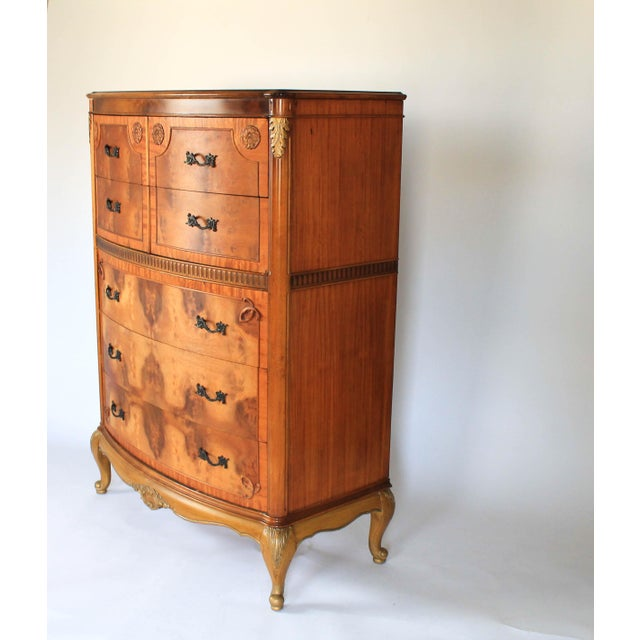 Louis XV-inspired bow front boudoir chest or tallboy dresser, circa 1930s. Features five bookmatched burlwood drawers with...