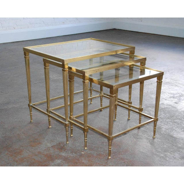 Circa 1950. A set of decorative and very functional nesting tables in brass and mirrored glass. Superb craftsmanship...