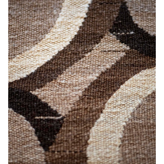 This handwoven flatweave rug has a shaded mole-brown field with an overall design of chocolate-brown, charcoal-brown and...