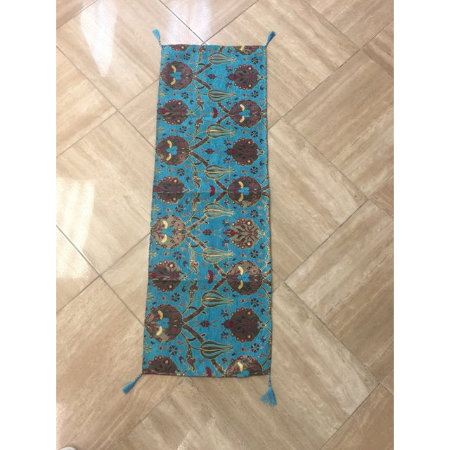 A Kilim motif table runner in turquoise. Fabric made from velvet and cotton Weaved by Turkic motifs Both end have...