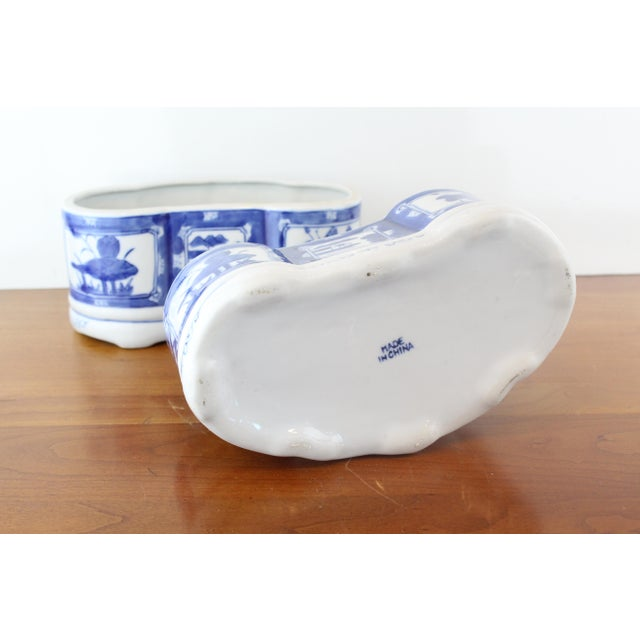 Pair of oblong shaped blue and white Chinese porcelain planters with floral and countryside details.