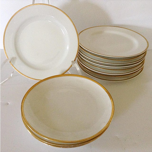 This is a set of 12 French bread and butter plates made by the Limoges factory. Each has an elegant gold rim that mixes...