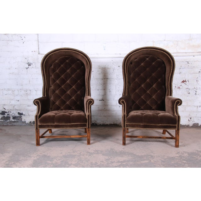 An exceptional pair of mid-century brown velvet hooded canopy Porter's chairs. The chairs feature solid wood legs and...