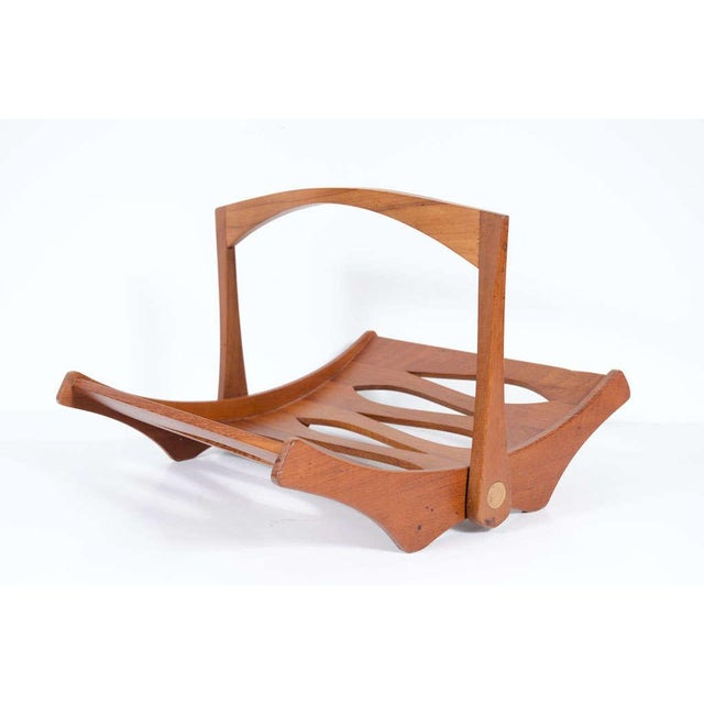 "A beautiful staved teak magazine rack with moveable handle and cut out forms to the body. Branded ""Staved Teak IHQ..."