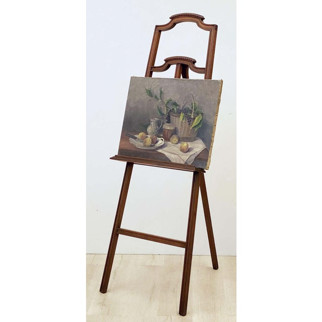 A fine English display or artist's easel, featuring a tripod stand with carved top panel, fixed gallery shelf, and wooden...