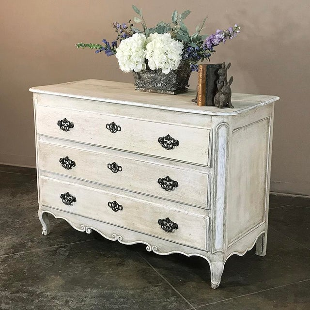 18th Century Country French Painted Commode features subtle rococo styling cues with the molded detail and the contoured...