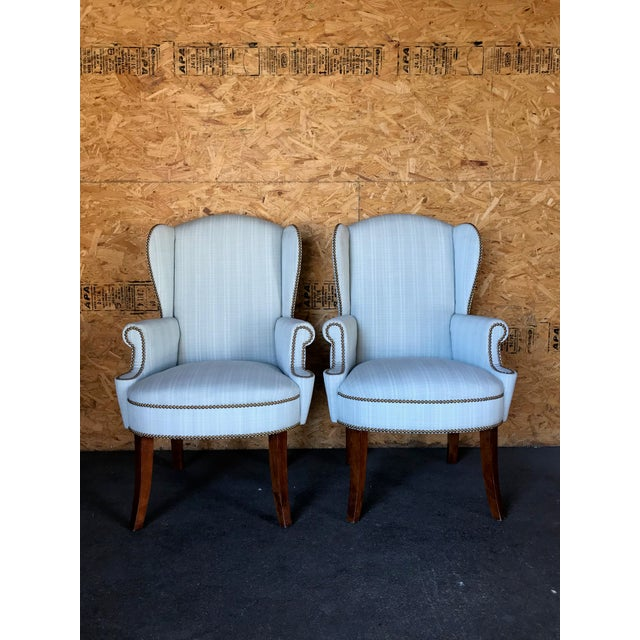 Comfortable traditional wingback captain chairs adorned with gold studding, white stripes, scrolled arms, and curved...
