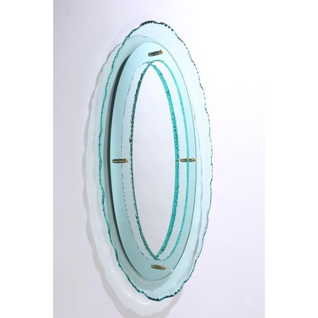 Oval hand-cut glass sculptural mirror framed mirror with brass details, after Fontana Arte. May be ordered in multiples....