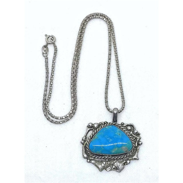 An artisan made, ornately designed sterling silver pendant bezel set with a hand-polished Kingman turquoise cabochon...