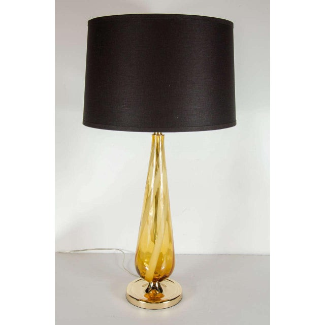 Mid-Century Modernist handblown Murano glass table lamp with an accentuated teardrop form featuring amber shaded Murano...