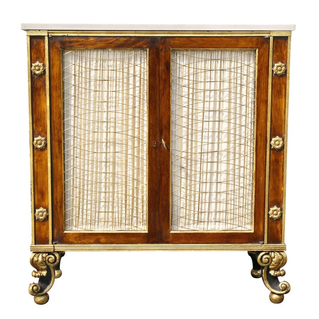 Antique credenza with a rectangular white marble top over a pair of grill doors flanked by panels with rosettes, raised on...