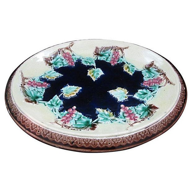 An antique scarce majolica platter with grapevines around a cobalt blue center. A raised Gothic border runs along the...