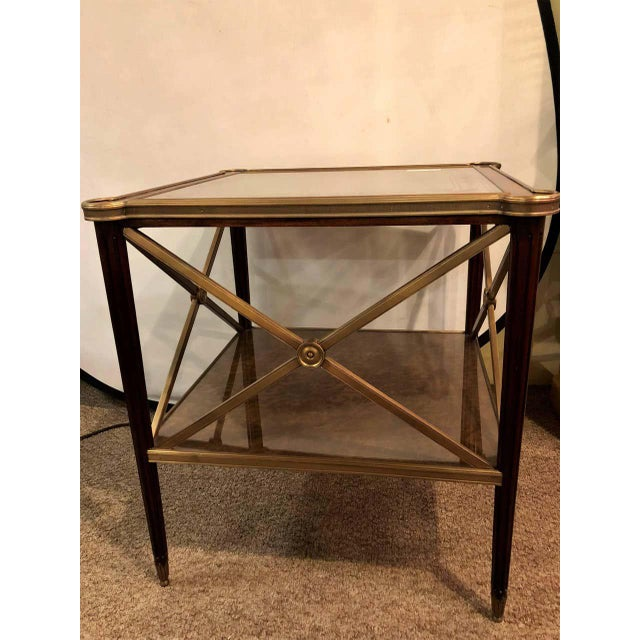A bronze decorated end table or nightstand with bronze X-base sides and a tortoise glass style top with matching lower...