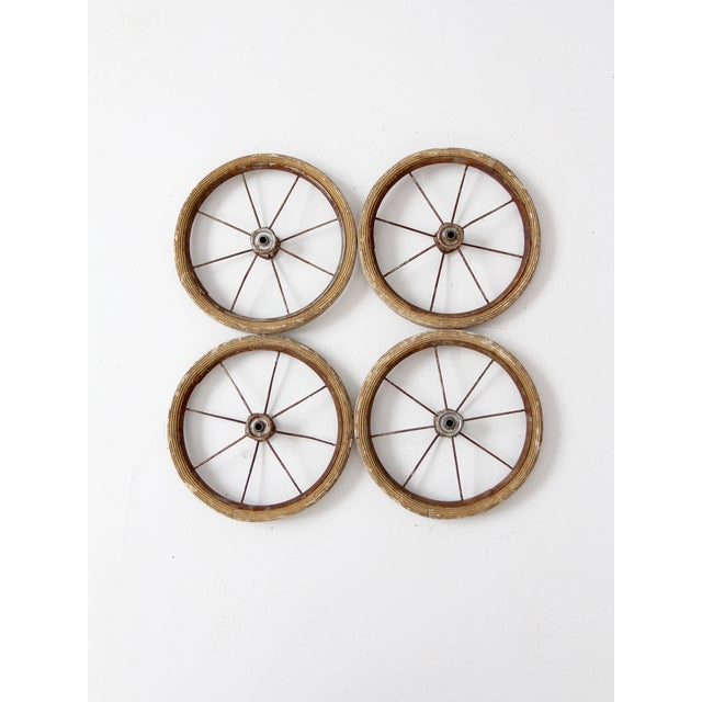 A set of 4 vintage doll carriage wheels. The small set of wheels features a metal and rubber frame with slender wire...
