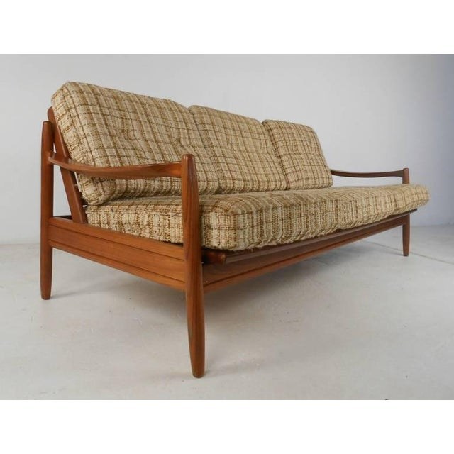 Well designed and constructed sofa and matching side chairs in solid teak. Graceful sloping arms with sturdy frames and...
