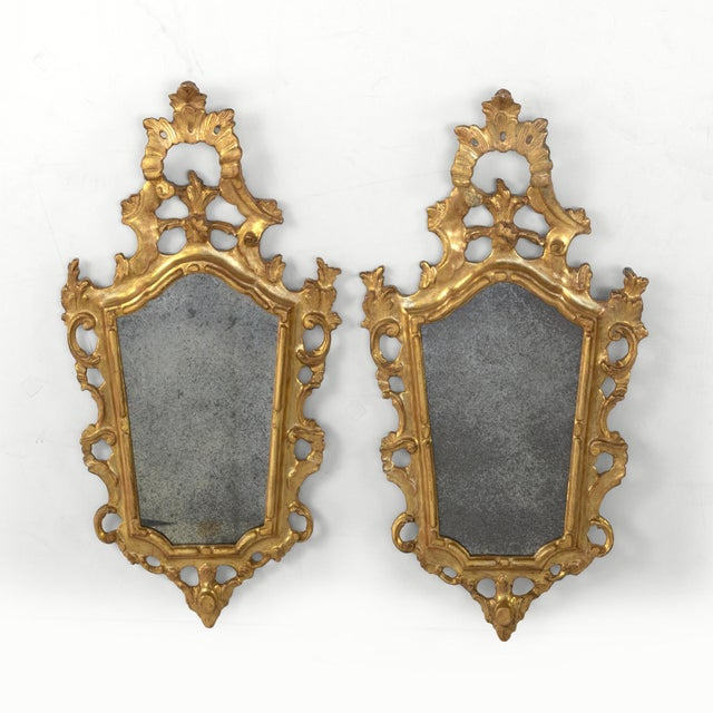 A small-scale pair of ornately-carved French gilt wood Rococo style mirrors; France, circa 1890 height: 26 in. 66 cm.,...