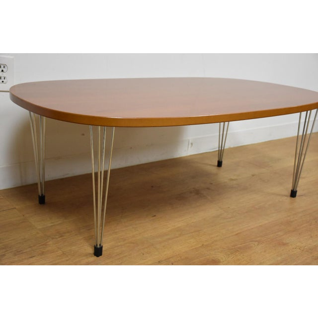 A mid century modern style Danish oval coffee table made of a cherry top and four legs which each consist of four chrome...