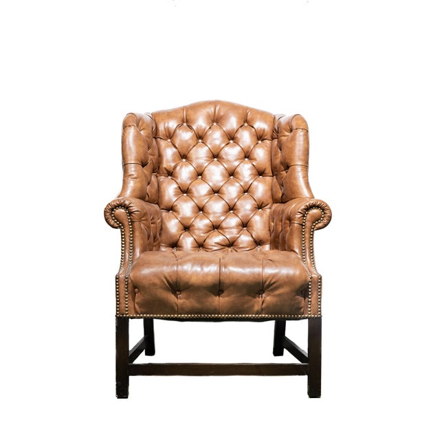 A pair of vintage wingback chairs with genuine tufted leather and wooden construction. The leather is of a burnt...